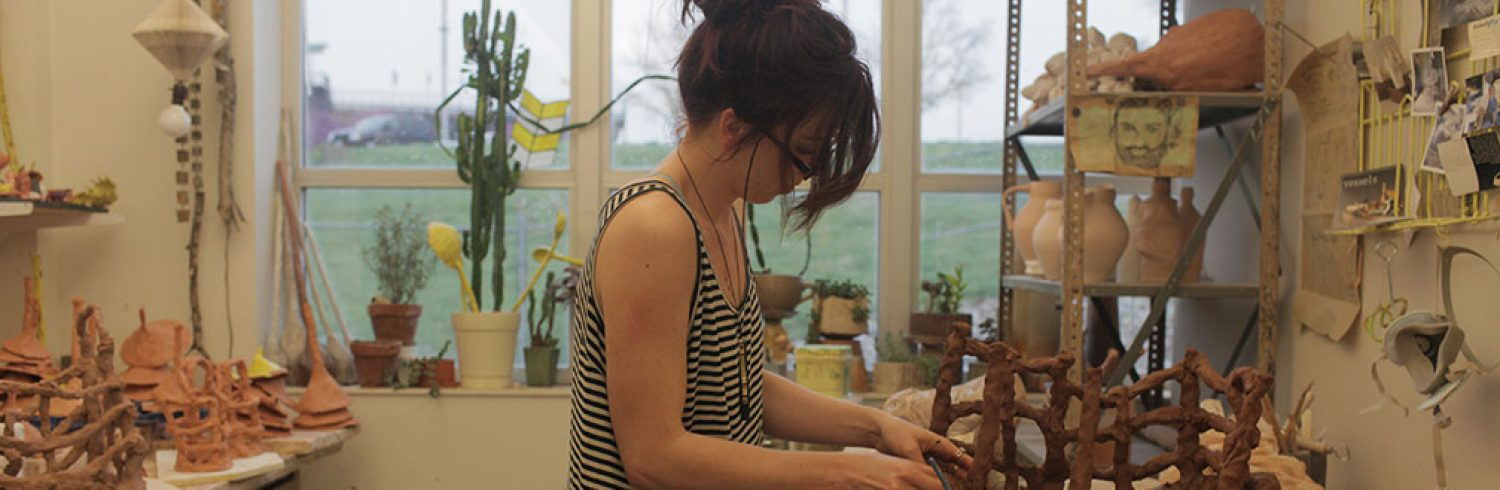 Graduate student Ginnifer O'Keefe work on her ceramic art. Her work was shown in the 2014 National Student Juried Exhibition in Milwaukee.