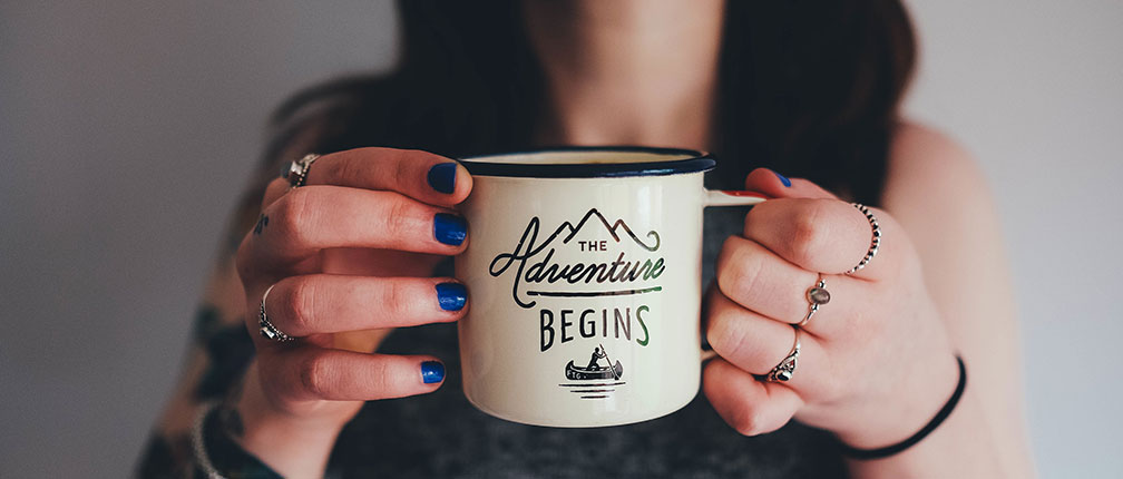 Woman with blue nail polish holding a mug that says