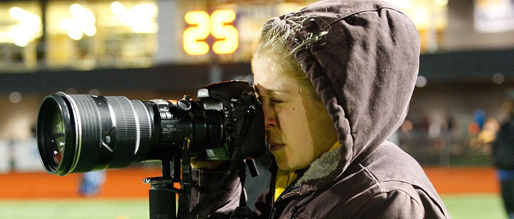 Student photojournalist taking photos at a Mizzou football game.