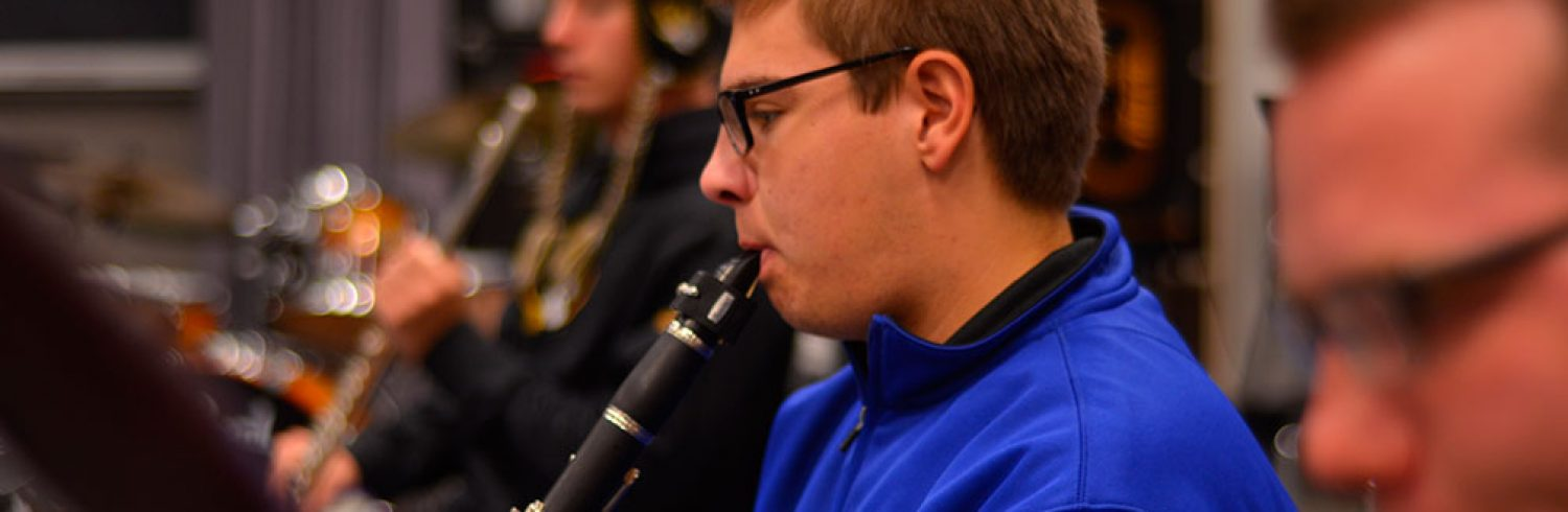 Student playing a clarinet in a classroom.
