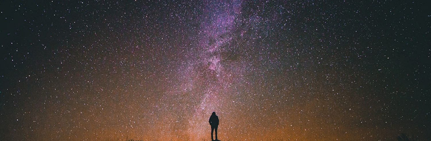 Silhouette of person standing in front of a starry night sky.